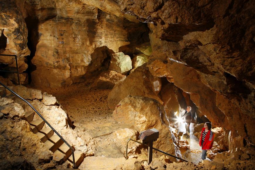 Blick von erhöhtem Standpunkt in eine große Höhlenkammer. Die Wände hinten und rechts bestehen aus bräunlichem, teils beleuchtetem Gestein. Links führt eine Steintreppe aufwärts, rechts ein schmaler Gang abwärts.