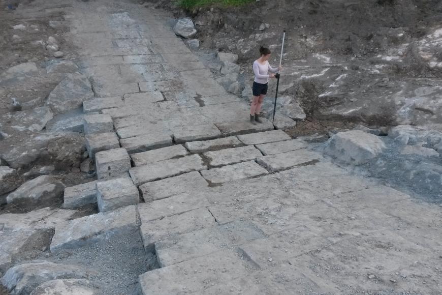 Zu sehen ist ein neu befestigter Weg aus großen Steinquadern, der durch ein trockenes Bachbett führt.