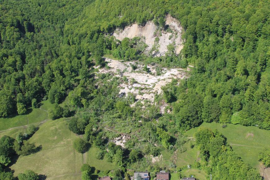 Luftaufnahme einer Rutschung inmitten eines großen Waldgebietes. Geröll und umgestürzte Bäume trafen dabei fast eine kleine Siedlung am unteren Bildrand.