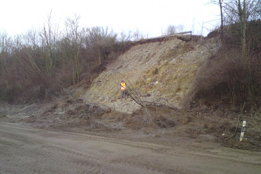 Das Bild zeigt die Böschung an einer Fahrbahn, die mit Büschen und niedrigen Bäumen bewachen ist. In der Mitte kommt aufgrund einer Rutschung hellbraunes bis hellgraues Material zum Vorschein. Unten befinden sich Lockermaterial und umgeworfene Sträucher.