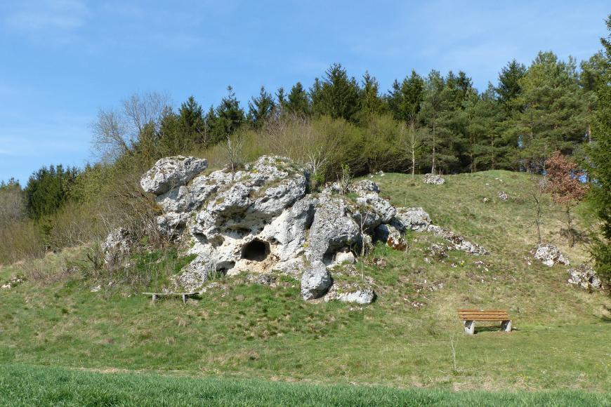 Hinter einer Wiese steigt ein grüner, rechts und hinten bewaldeter Hügel auf, in dessen Mitte ein unregelmäßig geformter Felsen herausragt. Der weißlich graue verwitterte Felsen weist Vorsprünge, Nischen sowie ein kleine Höhle auf.