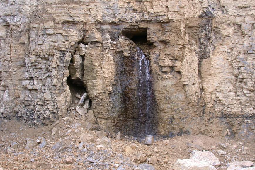 Das Bild zeigt eine hellbraune und zum Teil gräuliche Steinwand in deren Mitte Wasser aus einem Hohlraum fließt.