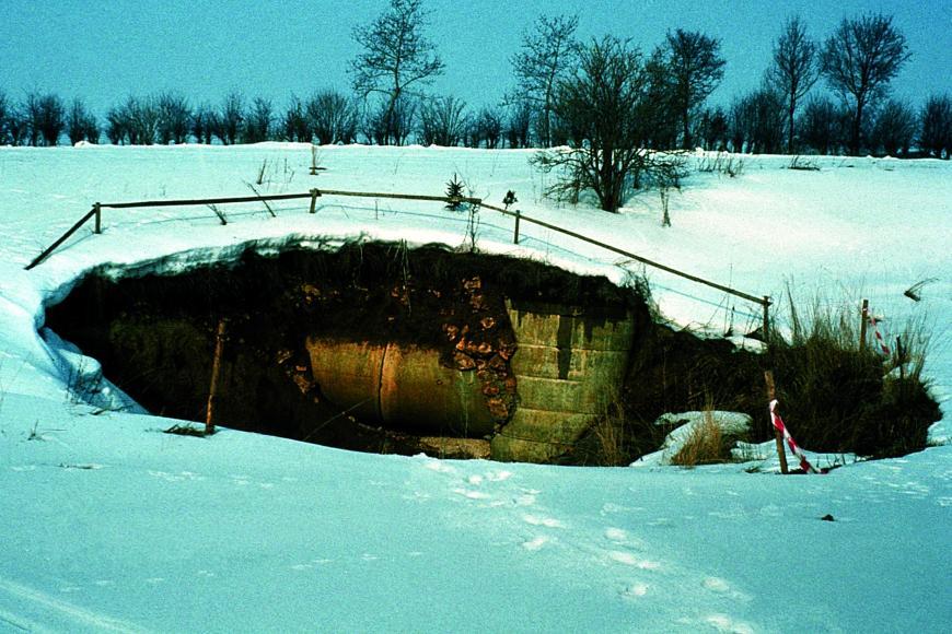 Das Bild zeigt eine schneebedeckte Landschaft. In der Bildmitte ist eine dunkle Senke im Boden, die von einem Zaun umschlossen wird.