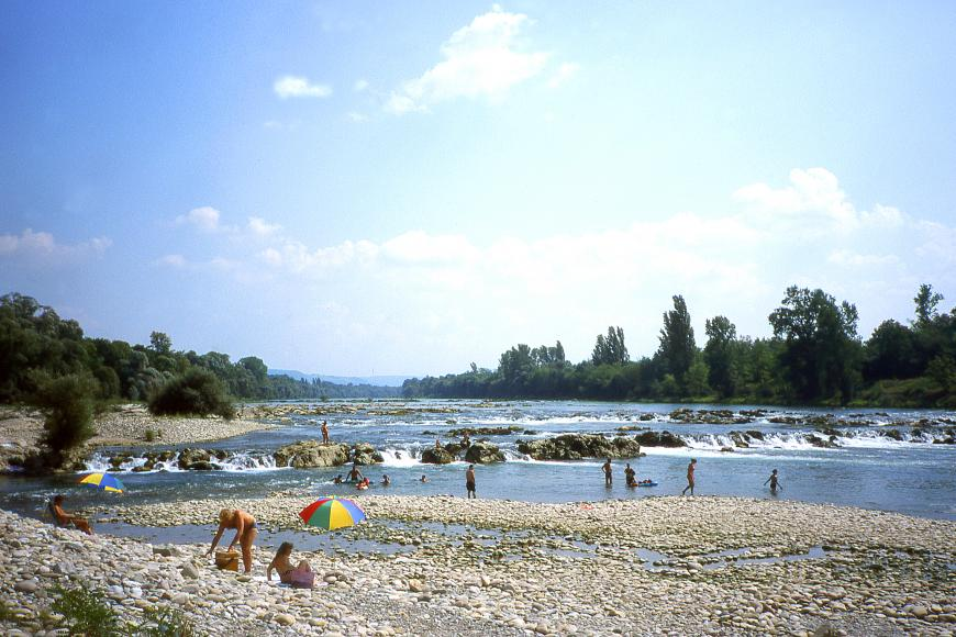Das Bild zeigt einen breiten, von zahlreichen kleinen und großen Felsen unterbrochenen Fluss. Den Vordergrund begrenzt ein steiniger Uferbreich. Mehrere Menschen baden in dem Fluss.