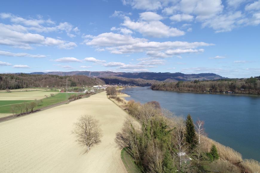 Von oben blickt man über helle Ackerflächen und Wiesen links sowie einen blauen Fluss rechts. Das rechte Ufer des Flusses ist bewaldet. Auch auf die Äcker und Wiesen folgt Wald. Im fernen Hintergrund erheben sich flache, bewaldete Berge.
