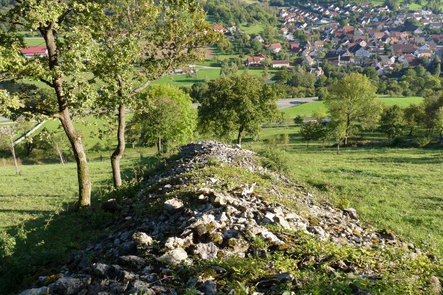 Ein auf einem Hang liegender, zur Mitte hin aufgehäufter Steinhügel bestimmt dieses Bild. Links und hangabwärts stehen Bäume; rechts blickt man auf die weit unten liegenden Dächer einer Ortschaft.