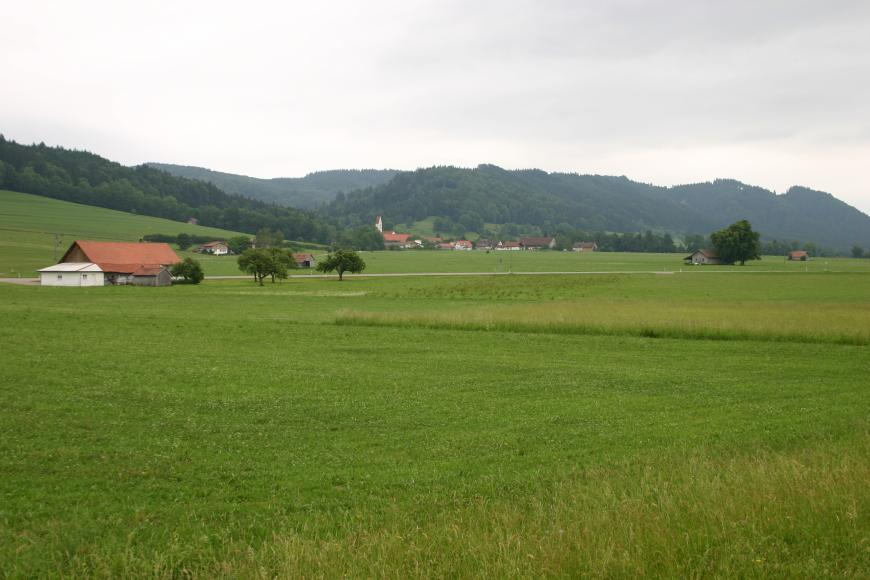 Im Vordergrund befindet sich eine große Wiese mit vereinzelten Bäumen und einem Bauernhof am linken Bildrand. Im Hintergrund ist eine kleine Siedlung und dahinter eine bewaldete Bergkette erkennbar.
