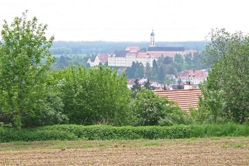 Blick auf eine weitläufige Klosteranlage, die auf einer Erhebung im Bildmittelgrund liegt. Zu Füßen des Klosters liegt eine Siedlung. Im Vordergrund Bäume sowie ein hoch gelegener Acker.
