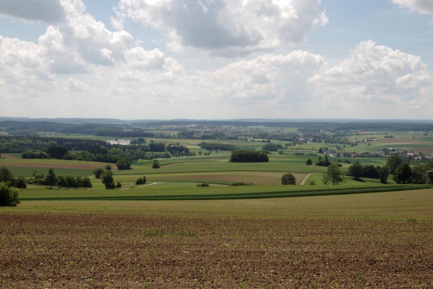 Blick von einem erhöht liegenden, mit jungem Grün bedeckten Acker auf weites grünes Hügelland mit vereinzelten Äckern, Waldstreifen und Siedlungen. Im fernen Hintergrund sind bewaldete Höhen erkennbar.