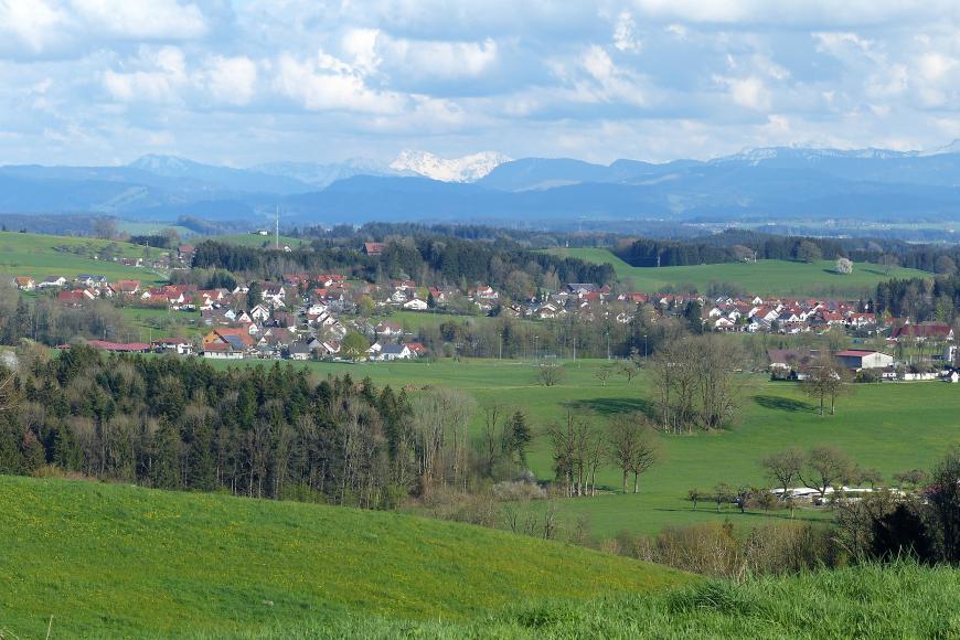 Panoramabild einer grünen Hügellandschaft mit Wiesen, Waldgebieten und Siedlungen. Im Hintergrund ist eine Kette schneebedeckter Berge erkennbar.