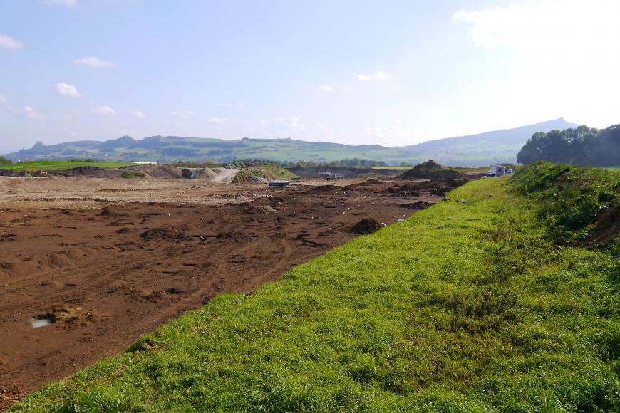 Links neben einer Wiese ist eine archäologische Grabungsfläche zu sehen. Im Hintergrund befindet sich eine Kiesgrube.