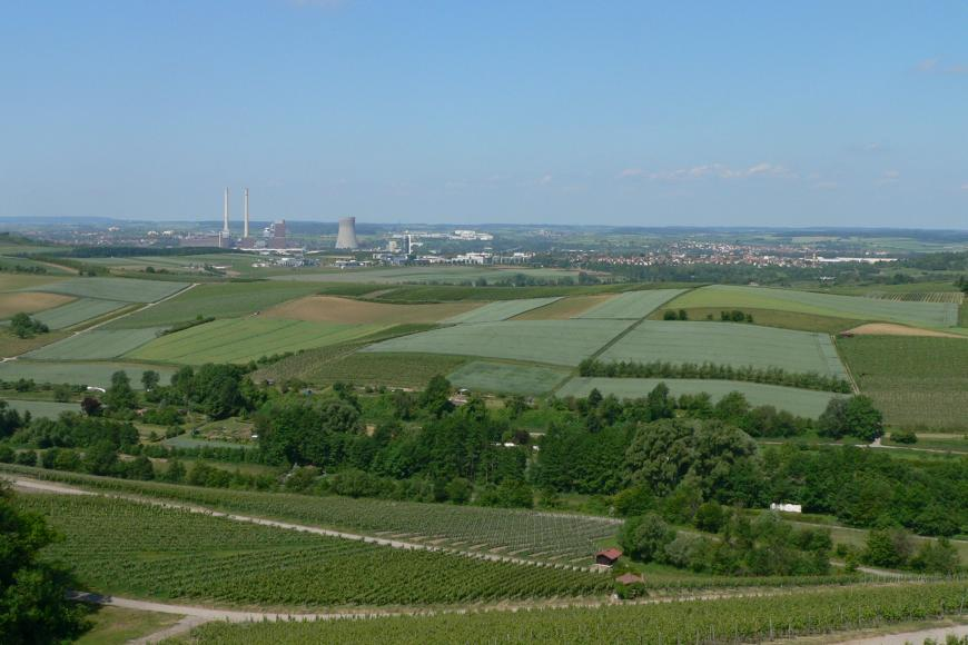 Von erhöhtem Standort blickt man über Rebterrassen im Vordergrund auf eine hügelige Landschaft mit einem Mosaik aus Wald und verschiedenen Äckern. Im Hintergrund links ist ein Kraftwerk erkennbar.