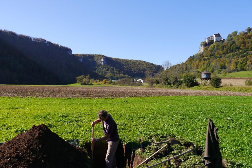 Das Bild zeigt das Aufgraben eines Bodenprofils inmitten einer ebenen Grünfläche. Im Hintergrund sind - jeweils zu den Rändern ansteigend - bewaldete Hänge erkennbar; links mit herausragenden Felsen, rechts mit einer Burg.