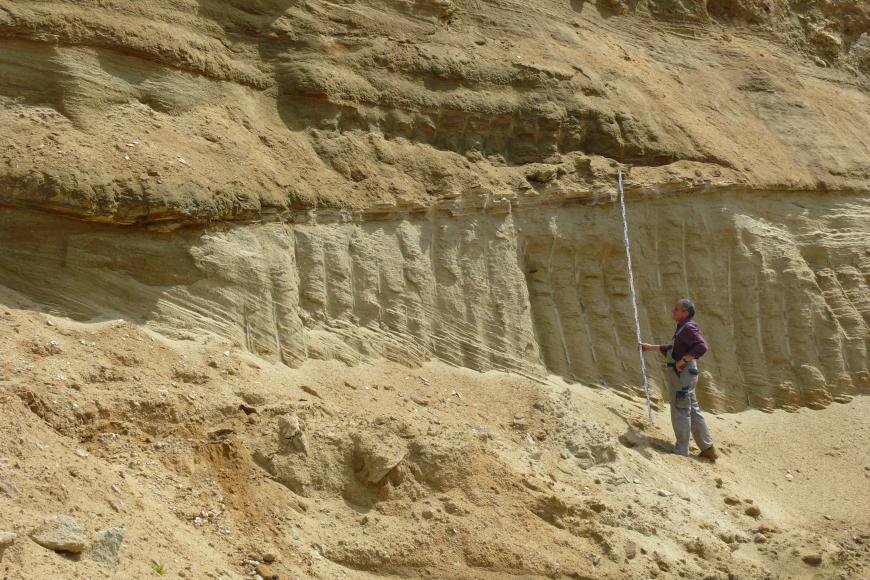 Blick auf eine gelblich braune, feinkörnige Gesteinswand, die durch säulenförmige Bildungen in der Bildmitte unterbrochen wird. Rechts hält ein Mann in Arbeitskleidung eine Messlatte hoch.