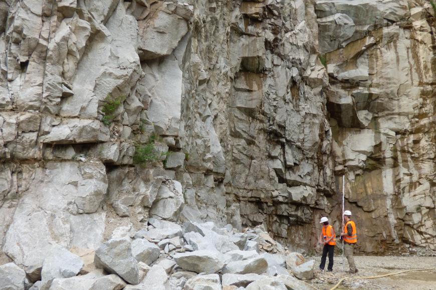 Blick auf mächtige, stark zerfurchte Steinbruchwände. Das Gestein, von dem links vorne größere Blöcke aufgehäuft sind, ist hellgrau bis dunkelgrau, rechts auch bräunlich grau gefärbt.