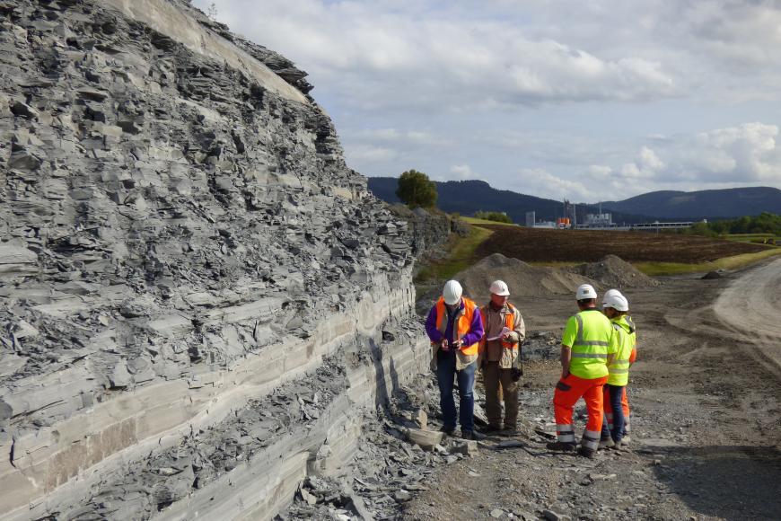 Blick in einen Steinbruch. Links im Bild erhebt sich eine steile, unten leicht abgestufte Gesteinswand. Das Material ist grau und splittrig. Rechts ist flacheres Steinbruchgelände sichtbar sowie vorne vier Arbeiter.