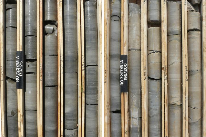Das Bild zeigt eine Bohrsequenz, aufgeteilt in 10 nebeneinander stehenden Kästen, aus dunkelgrauem (links) bis braunem (rechts) Gestein. Ganz links und mittig befinden sich 2 kleine Schilder mit Beschriftung.