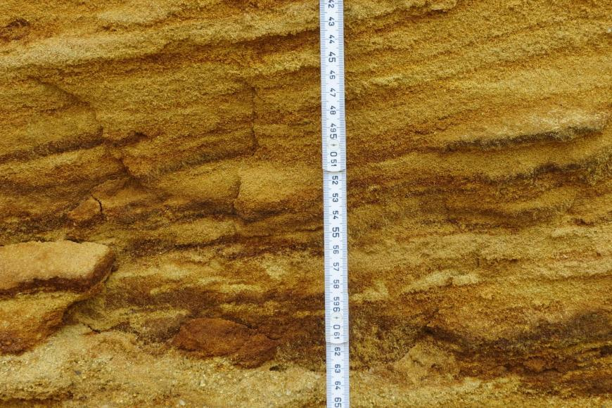 Nahaufnahme von streifigen, gelblichen und rötlichen Sandlagen. In der Bildmitte ist ein Maßstab angelehnt.