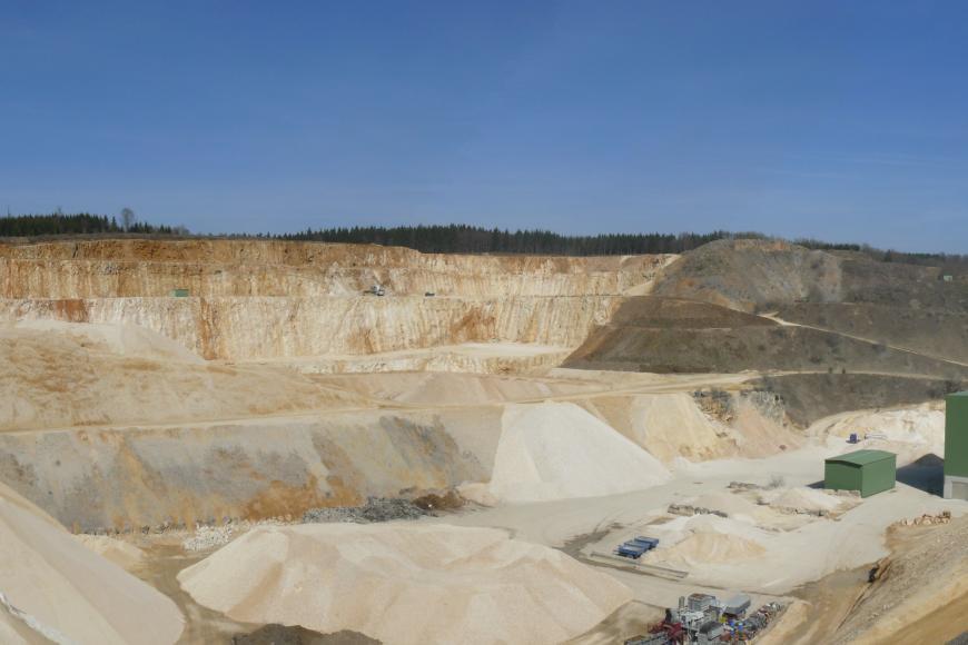 Blick in einen großen Steinbruch mit aufgehaldeten hellbeigen Splitten und Schottern auf der untersten Sohle.