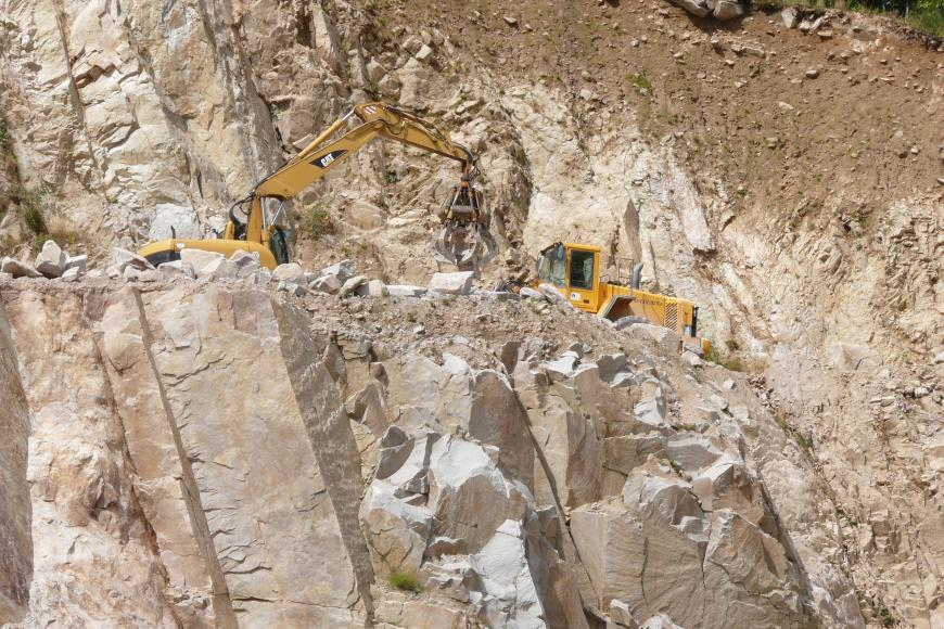 Blick in einen Steinbruch: Das hellbeige bis hellgraue Gestein ist stark geklüftet, dabei stehen die Klüfte sehr steil. Zwischen den Felswänden befindet sich - halb verdeckt - ein gelber Bagger.
