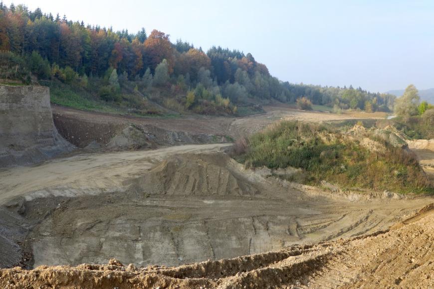 Übersichtsbild einer Kies- und Sandgrube mit hohen Abbauwänden links, niedrigen und offenen Wänden rechts sowie Abraumhalden in der Bildmitte. Im Hintergrund links steht Wald an.