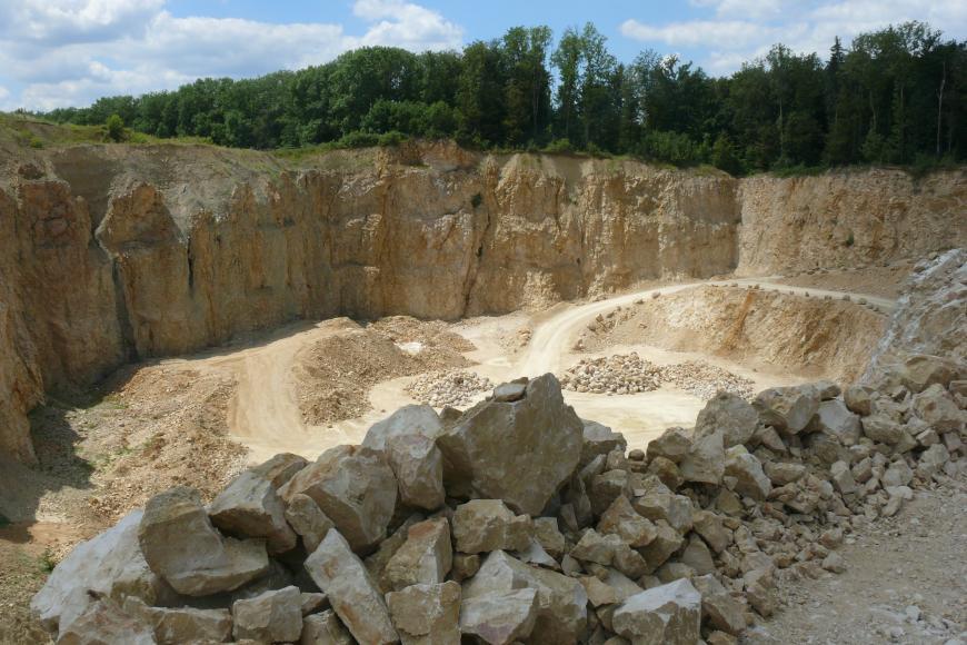 Blick von schräg oben in einen Steinbruch. Das anstehende Gestein ist gelblich-beige. Die Höhe der Abbauwand nimmt von links nach rechts ab, im rechten Teil wächst Wald über der Wand. Im Vordergrund des Bildes liegt Geröll.
