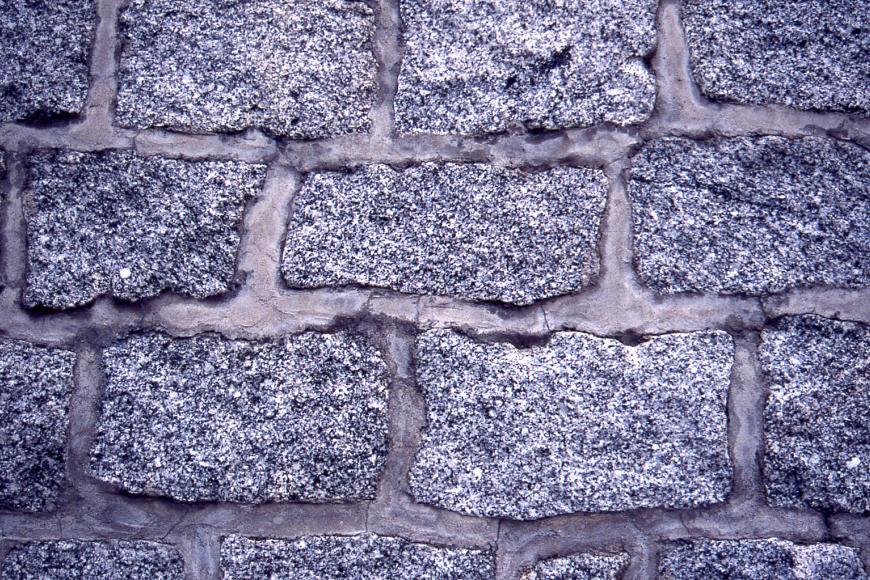 Nahaufnahme einer Mauer. Die einzelnen Blöcke sind ungefähr gleich groß und alle rechteckig, sie sind rötlichgrau und gleichkörnig.