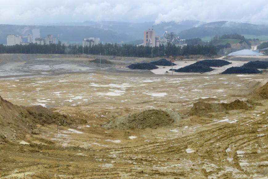Panoramabild von erhöhtem Standpunkt, welches einen Steinbruch zeigt. Das anstehende Gestein ist schmutzig gelb. Im Hintergrund sind Industrieanlagen zu erkennen.