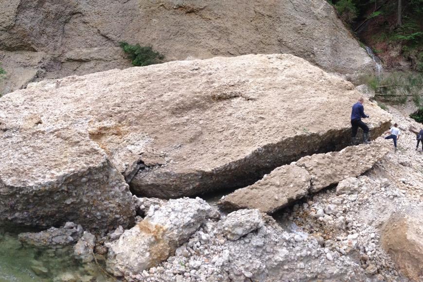 Zu sehen ist ein sehr großer und mehrere kleinere Felsblöcke, die vor einer Felswand liegen. Vor den Felsblöcken fließt ein Bach. Rund um den Gesteinsblock herum sind einige Personen zu erkennen, die den mächtigen Block bestaunen.