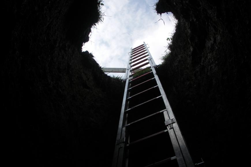 Der Blick richtet sich von der Sohle eines Schachtes nach oben durch die ellipsenförmige Öffnung. Eine Leiter ragt über den Rand des Schachtes hinaus.