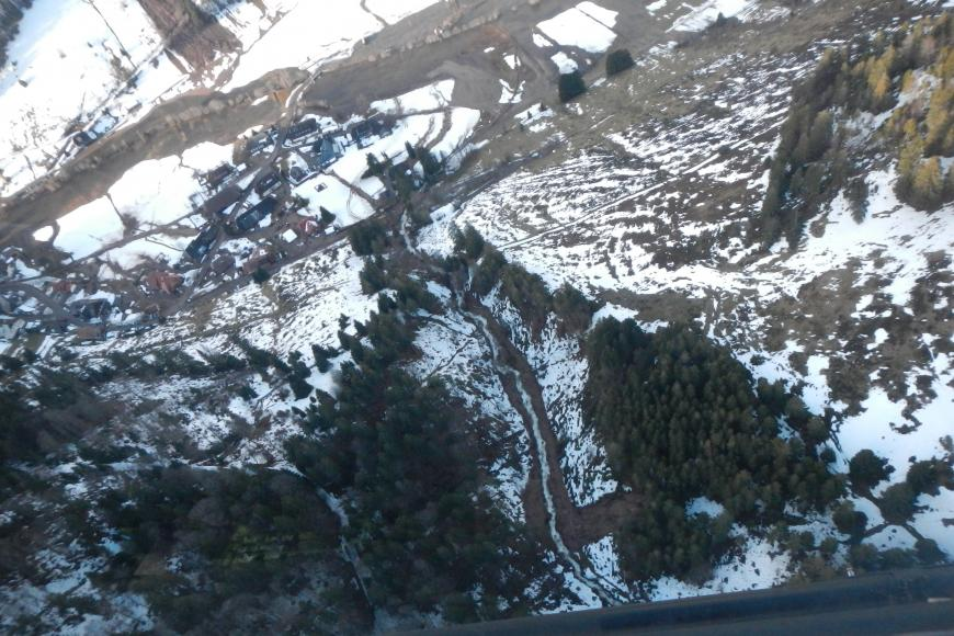 Blick aus dem Fenster eines Hubschraubers auf einen teilweise schneebedeckten Hang mit einigen Bäumen. Der Hang ist von einem Bachbett durchschnitten. Am oberen Ende des Hanges ergießt sich braunes Erdreich in den Bach.