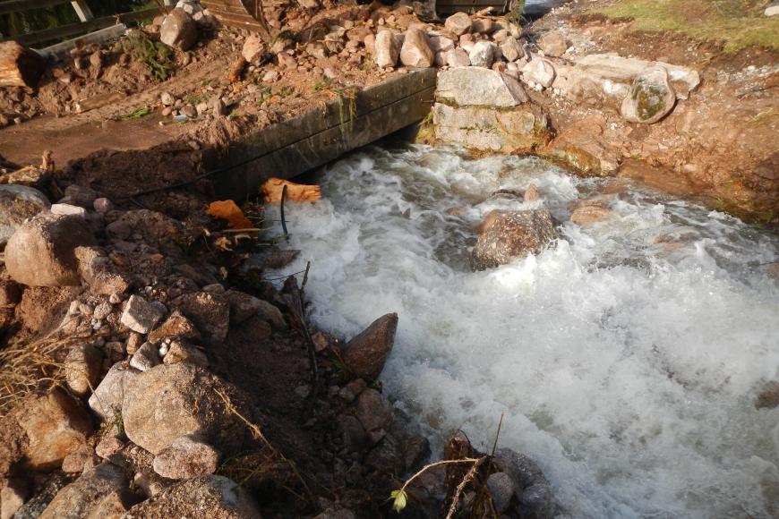 Zu sehen ist eine Brücke, unter der ein stark angeschwollener Bach fließt. Unterhalb der Brücken befinden sich rechts und links des Gewässers einige große Steine und Geröll. Auf der Brücke werden gerade Steine und Schlamm von einem Bagger weggeräumt.