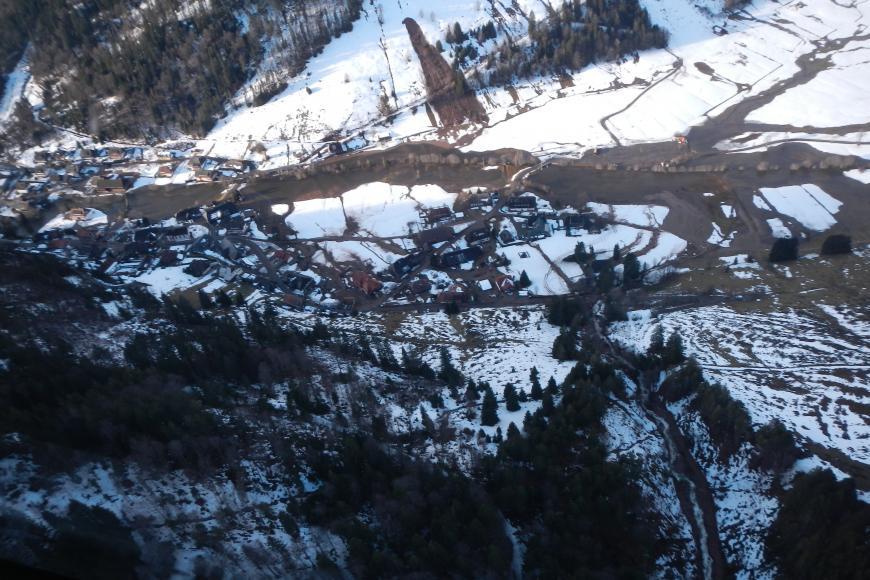 Blick aus der Luft auf ein Tal mit Ortschaft, durch die ein Fluss fließt. An den sich gegenüberliegenden, teilweise schneebedeckten und teils bewaldeten Hängen lassen sich am unteren Bildende ein Murgang, am oberen Bildende eine weitere Hangmure erkennen.