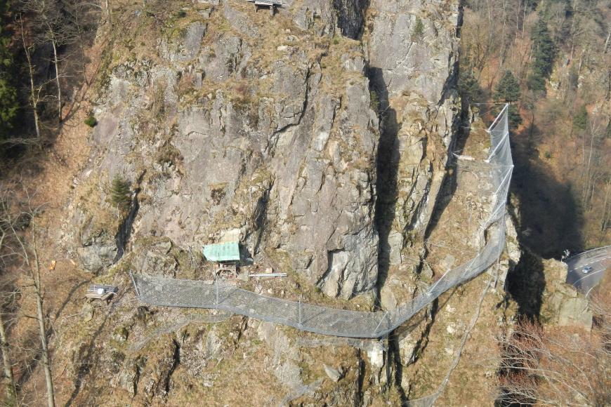 Zu sehen ist eine Felswand, die oberhalb bewaldet ist. Etwa auf der Hälfte des Felsens befindet sich ein Zaun, der sich fast über die gesamte Länge des Felsen zieht.