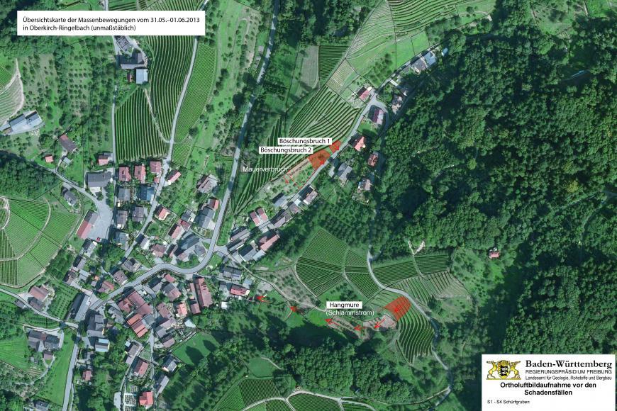 Bearbeitetes Luftbild einer Hanglandschaft mit Siedlung, das in der Bildmitte und rechts darunter Böschungsbrüche sowie eine Hangmure erkennen lässt.