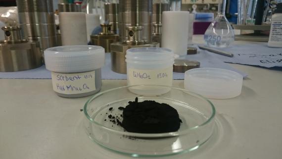 Das Bild zeigt im Vordergrund eine flache gläserne Schale, die eine dunkle Substanz enthält, sowie mehrere beschriftete Behälter. Im Hintergrund sind Einrichtungsgegenstände eines Labors zu erkennen.