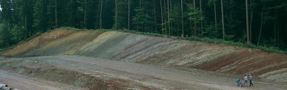 Blick auf eine Straßenbaustelle mit einer nach links an- und wieder absteigenden Rampe und einem angeschnittenen, bewaldeten Hang im Hintergrund. Der Hang weist schräg verlaufende, unterschiedliche Farben auf.