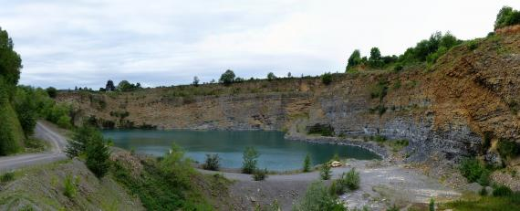 Panoramabild eines Steinbruches mit hinterer und rechter Bruchseite, einem See davor und Fahrwegen links und im Vordergrund. Die Bruchwände sind gelblich bis rötlich braun, durchsetzt von grauen Abschnitten.