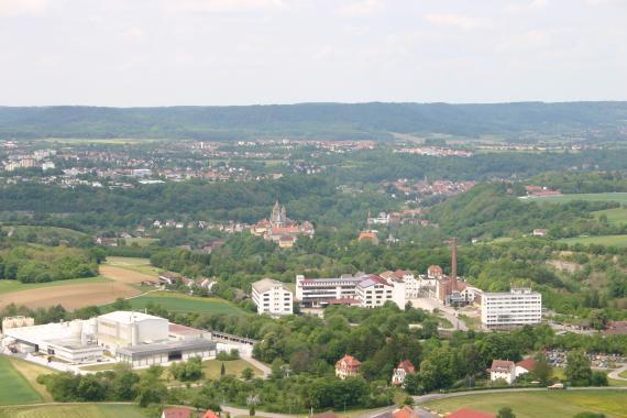 Blick aus großer Höhe über eine weite, hügelige Landschaft, in der sich zwischen ausgedehnten Waldflächen immer wieder Siedlungen zeigen. Im Vordergrund liegen Industrieanlagen. Im Hintergrund steigen bewaldete Berge mit flachen Rücken auf.