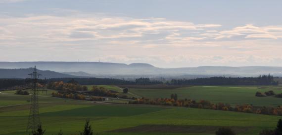 Von erhöhtem Standort blickt man über eine weite, flachhügelige Landschaft mit Äckern und Wiesen. Mehrere Waldstreifen durchziehen das Gelände. Im Hintergrund sind bewaldete Berge erkennbar.