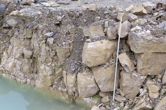 Detailaufnahme einer Steinbruchwand. Rechts liegen größere Blöcke scheinbar lose aufeinander. Dazwischen und links davon ist Schutt nachgerutscht. Noch weiter links sind die Blöcke kleiner. Am Boden des Bruches steht Wasser.