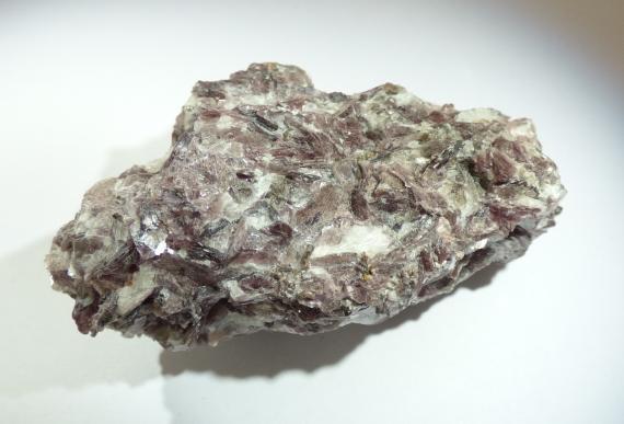 Nahaufnahme eines Handstückes von Mineralgestein vor hellem Hintergrund. Der Gesteinsbrocken zeigt verschiedene Farbnuancen, von grau über gelbgrün bis rosaviolett. Auch weißliche Flecken sind erkennbar.