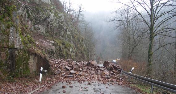 Im Vordergrund befindet sich eine Straße, die von Blöcken und Steinen bedeckt ist. Links befindet sich eine steile Flanke, an der Festgestein ansteht.