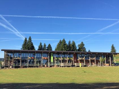 """Blick auf einen modernen Flachbau mit Glasfront und Veranda. Das Gebäude trägt den Schriftzug """"Haus der Natur"""" und steht auf einer Wiese mit Nadelbäumen dahinter. Am Himmel sind zahlreiche rechteckige Kondensstreifen zu sehen."""