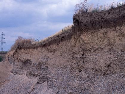 Seitenansicht einer sich nach links verjüngenden Kiesgrube mit dunkler Kuppe. Links unten sind Kieshänge erkennbar.