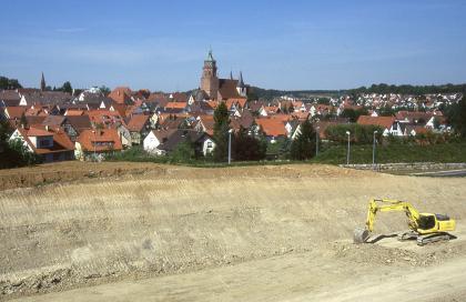 Im Vordergrund des Bildes ist ein großer, gelblich brauner und grauer Hügel zu sehen, den ein Bagger an Sohle und Seite bearbeitet hat. Direkt dahinter breitet sich eine Stadt aus.