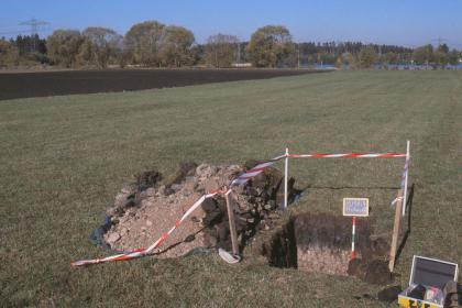 Das Foto zeigt rechts im Vordergrund ein aufgegrabenes Bodenprofil inmitten einer ebenen Grünlandfläche. Grube und Aushub haben sowohl sehr helle als auch sehr dunkle Bodenanteile.