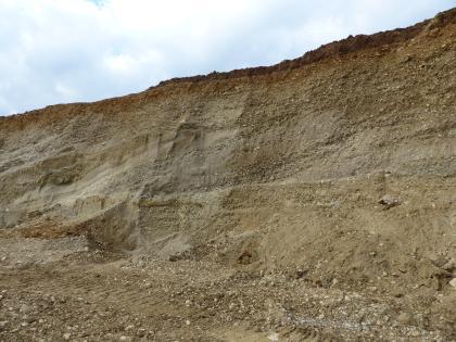 Das Bild zeigt eine Kiesgrube mit nach links verlaufender Neigung. Die Abbaufläche ist hellbraun gefärbt.