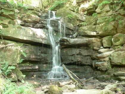 Blick auf mehrere Lagen grünlich grauer, größerer und kleinerer Blocksteine, über die in der Bildmitte ein schmaler Wasserfall fließt.