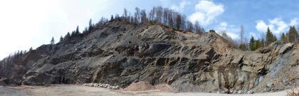 Blick auf eine langgestreckte Steinbruchwand aus schwarzgrauem bis braunem Gestein. In der Bildmitte hat die Bruchwand eine bergähnliche Form; insgesamt erinnert die Bruchwand an eine schlafende Echse.